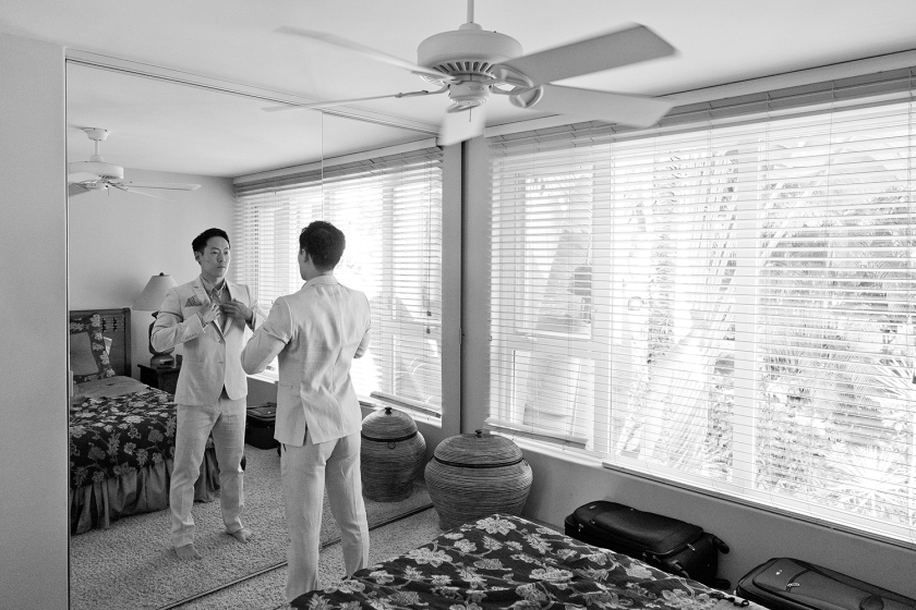 Black and white photograph of groom looking in mirror and finishing up the final touches as he gets dressed for his big day.