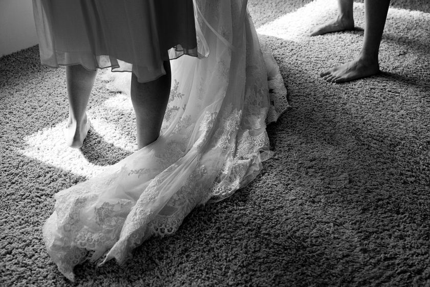 Black and white photograph showing the long lace detailed train of bride's wedding gown as she gets dressed for her big day.