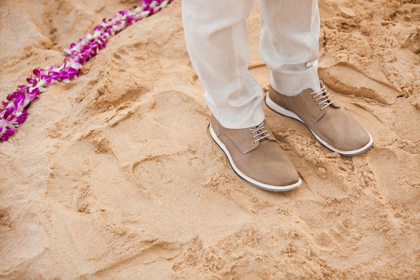 Groom's feet as he stands in the sand in a circle of purple orchid leis awaiting his bride.