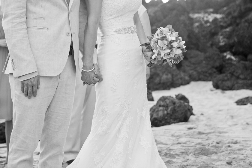 Black and white photograph of couple holding hands during wedding ceremony.