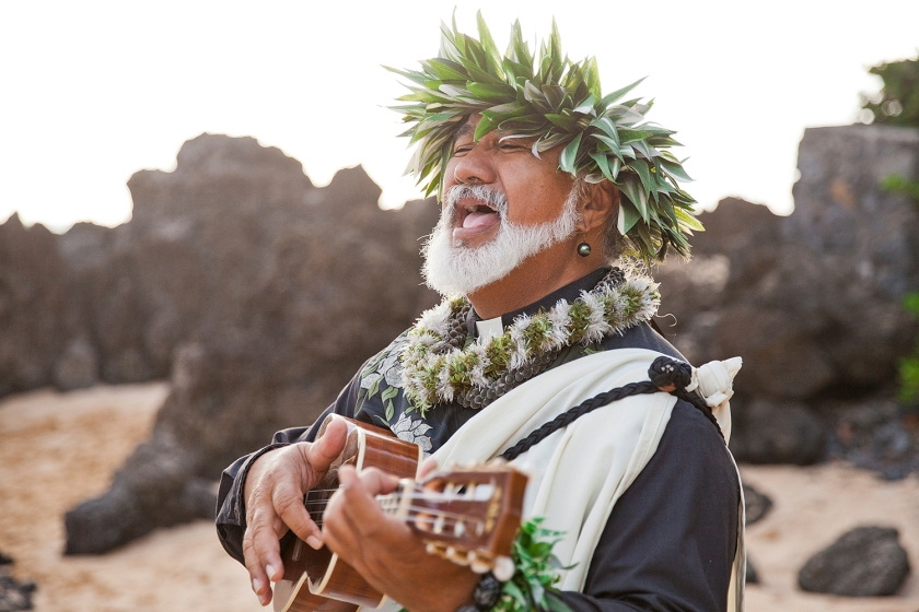 Officiant Laki Ka'ahumanu singing and playing the ukulele while newlywed couple have their first dance.
