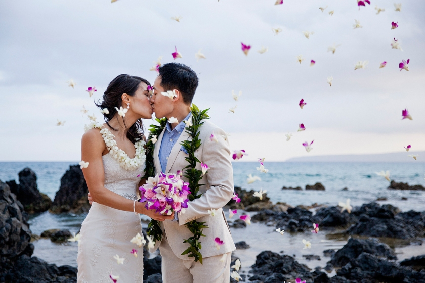 Newlywed couple embracing in kiss while purple orchids float down around them.