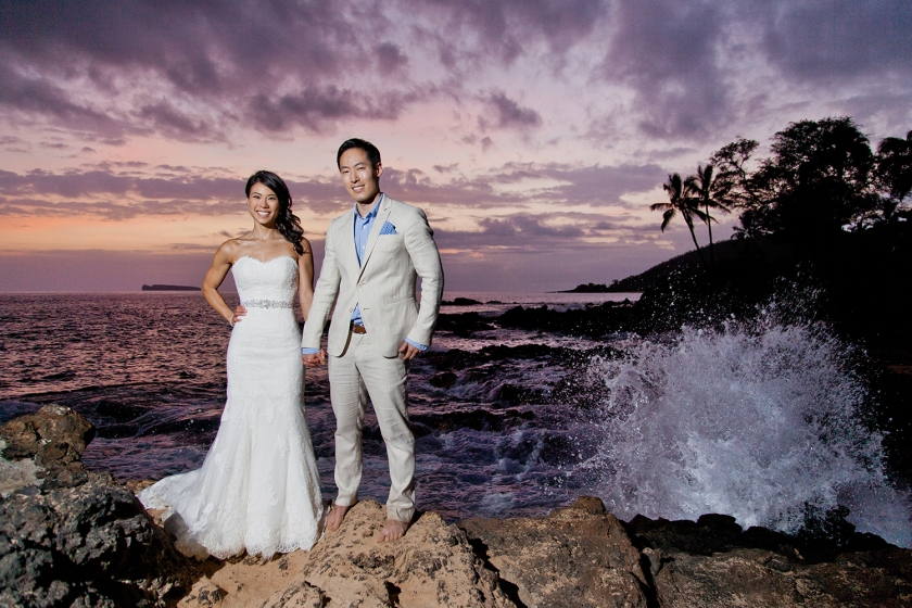 Newlyweds stand together on lava rocks reaching into the ocean at Makena Cove while Maui shows off her beautiful array of sunset colors.